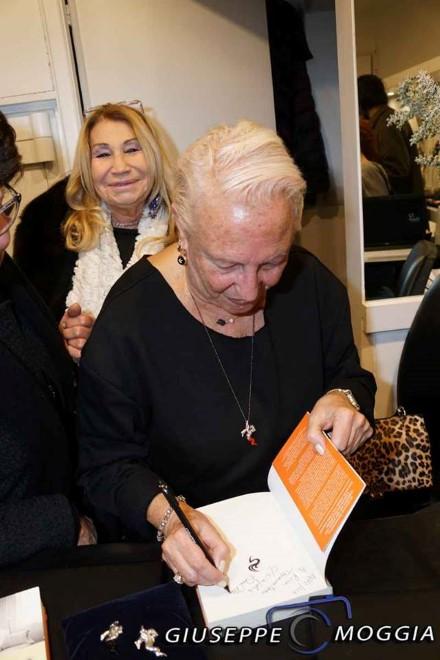 Annamaria Ghedina firma autografi del suo libro vicino al fantagioiello. Foto di Giuseppe Moggia.