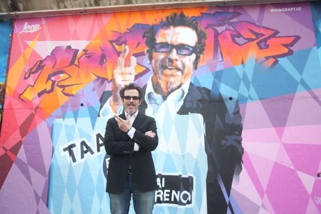 Germano Lanzoni davanti ad un murales che lo ritrae. Foto da Ufficio Stampa