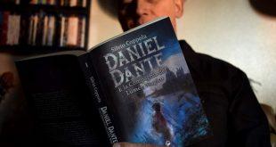 Silvio Coppola mentre sfoglia il suo libro Daniel Dante e la compagnia del Lumen magico